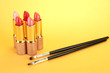 Lipsticks and brushes on yellow background