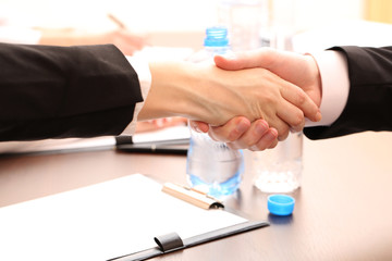 Business people shaking hands, on office background