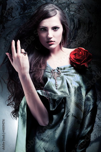 attractive woman in green drapery with red rose