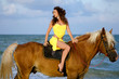 Pretty young woman riding a horse