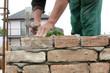 Mason making wall with mortar and bricks