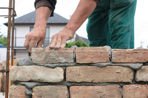 Mason making wall with mortar and bricks
