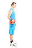 Full length portrait of a basketball player standing with a ball