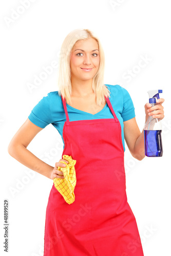 Female cleaner holding a liquid for spraying and a cloth