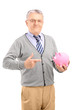 Satisfied mature gentleman holding a piggy bank and gesturing