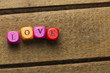 Word love on multicolored wooden cubes on wood