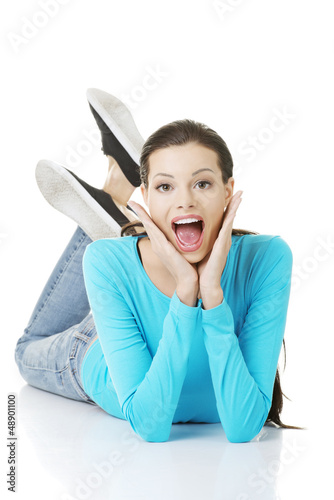 Happy woman in casual clothes lying on floor