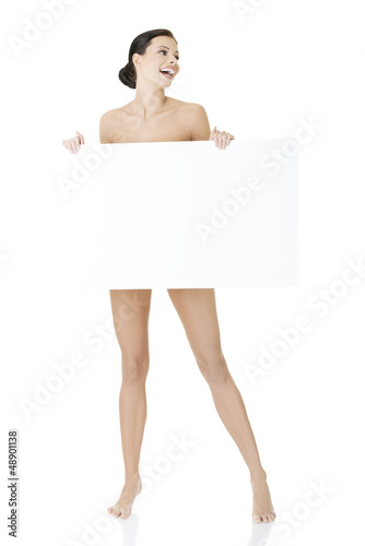 Sexy naked brunette holding empty board