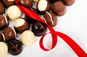 Assortment of dark and white chocolate candies with red ribbon