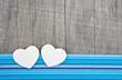 Zwei weiße Herzen als Glückwunschkarte auf Holz mit Blau