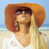 Beautiful blonde woman on the beach in sunglasses