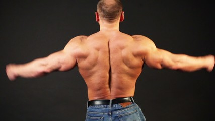 Bodybuilder shows his muscular body from behind and then turn