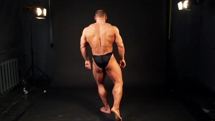 Bodybuilder shows his muscular body in small dark studio
