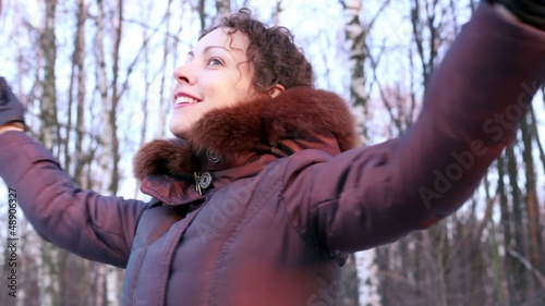 Young woman circling at background of birches