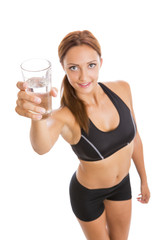 Fitness woman holding a glass of water. Selective focus.