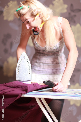 Housewife irons clothes and makeup corrects