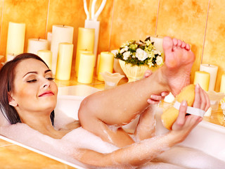 Woman wash leg in bathtube.