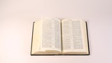 Bible (uncopyrighted book) lies on white table, pages are looked