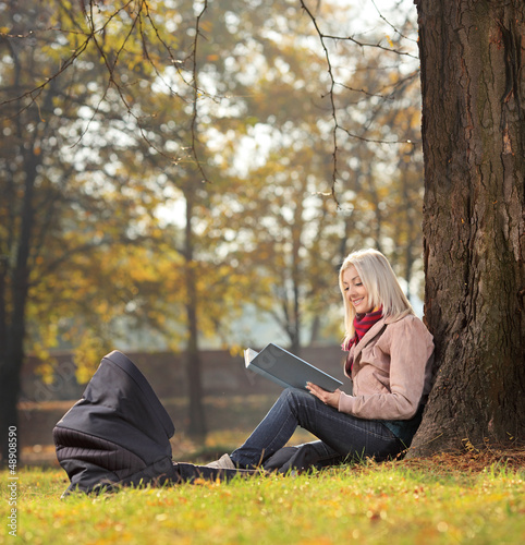Young mother sitting in a park reading a book with a baby in a c