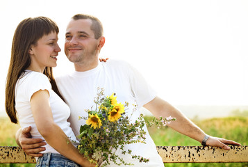 Happy young smiling couple with flowers