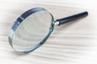 Magnifying glass magnifying glass on a wooden texture.