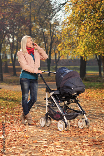 Young mother talking on a phone during a walk with her baby