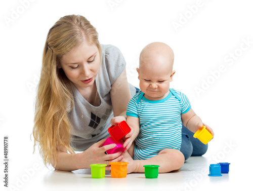 baby boy and mother playing together with cup toys