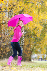 woman wearing rubber boots with umbrella in autumnal nature