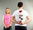 loving man holding red rose for his woman on grey background