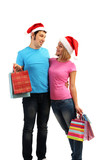 Young couple in Santa hats shopping and holding many shopping