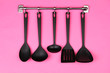 Black kitchen utensils on silver hooks, on pink background