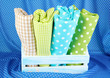 Color mottled fabrics in basket on blue fabric background