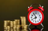 Alarm clock with coins on dark background