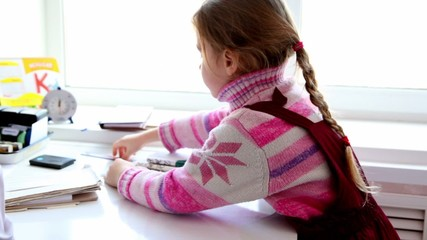 Little girl sit at doctors table in front of window