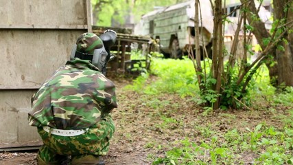 Boy paintball player sits in ambush in at background of old