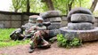 Two boys paintball players sit in ambush behind pile of tyres
