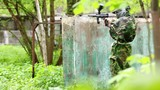Boy paintball player sits in ambush behind metal fence, then