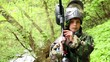 Boy stands with paintball gun at background of green leaves