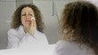 Woman wearing white bathrobe cleans face in front of mirror in