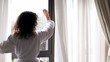 Woman comes to draws curtains and watch street outside window
