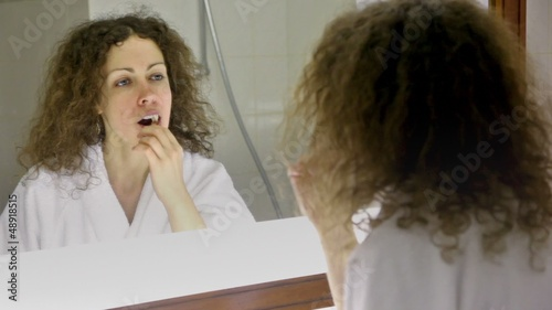 Woman wearing white bathrobe brushes teeth in front of mirror