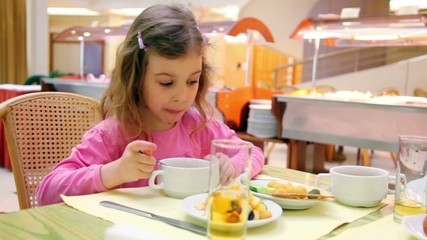 Little girl sits at table and eats breakfast in cafe
