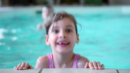 Little girl jumps in water near edge of pool, her brother at
