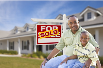 Father and Son In Front of Sold For Sale Sign and House