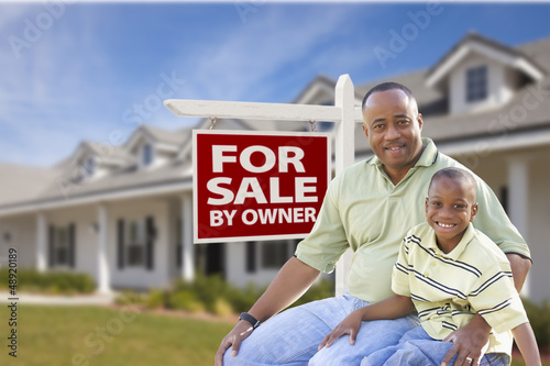 Father and Son In Front of For Sale By Owner Sign and House