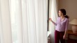 Young woman draws curtains and opens window with city street