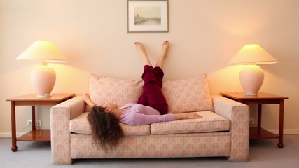 Young woman lies on sofa and shake legs at room with lamps on