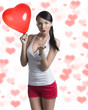 sexy brunette with heart shaped balloon sends a kiss