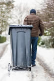 Man moving dustbin in the snow