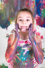Mädchen bemalt sich mit Fingerfarben